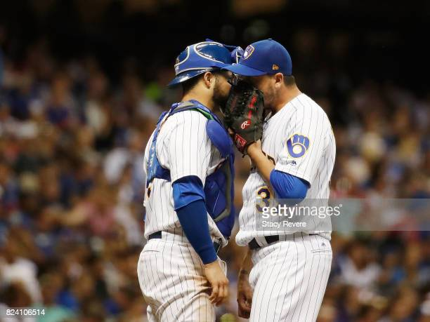 Anthony Swarzak of the Milwaukee Brewers speaks with Manny Pina during the eighth inning of a game against the Chicago Cubs at Miller Park on July 28...