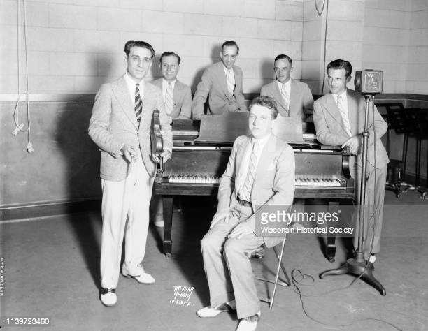Anthony 'Tony' Salerno's Gypsy Melodians at WIBA radio station standing around a piano Madison Wisconsin August 23 1932 Tony is holding his violin...