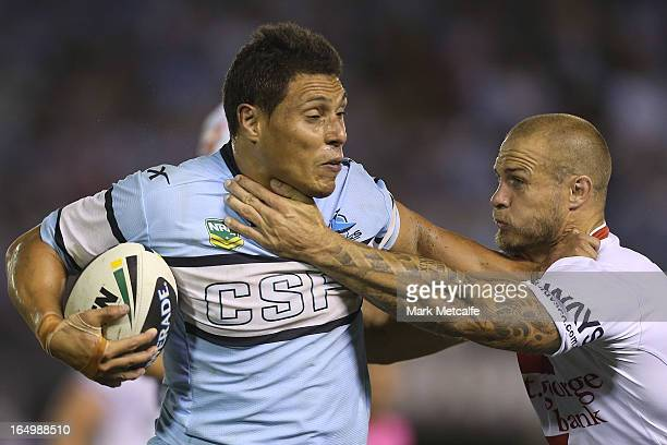 Anthony Tupou of the Sharks hands off Matt Cooper of the Dragons during the round four NRL match between the Cronulla Sharks and the St George...