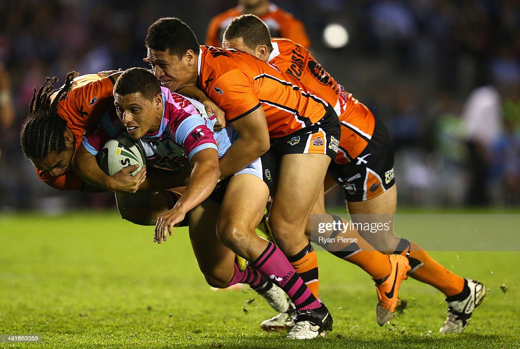 Anthony Tupou of the Sharks is tackled by Martin Taupau and Sauaso Sue of the Tigers during the round 10 NRL match between the Cronulla-Sutherland Sharks and the Wests Tigers at Remondis Stadium on May 17, 2014 in Sydney, Australia.