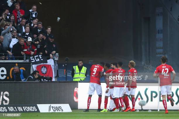 Anthony Ujah of 1 FSV Mainz 05 celebrates with his team mates after scoring his team's first goal as Eintracht Frankfurt supporters throw beers...