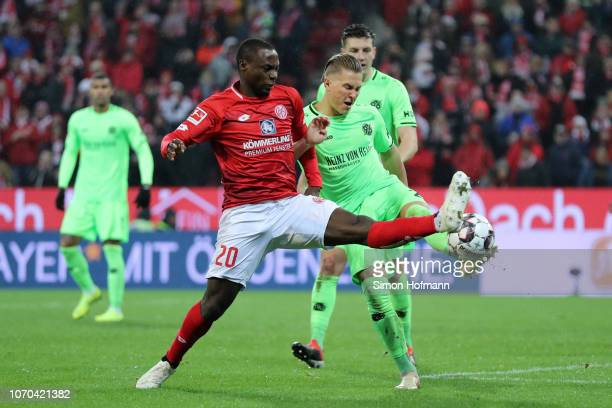 Anthony Ujah of FSV Mainz is challenged by Matthias Ostrzolek of Hannover 96 during the Bundesliga match between 1 FSV Mainz 05 and Hannover 96 at...