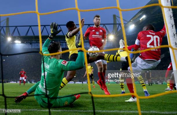 Anthony Ujah of FSV Mainz shoots under pressure from DanAxel Zagadou and Roman Buerki of Borussia Dortmund during the Bundesliga match between...