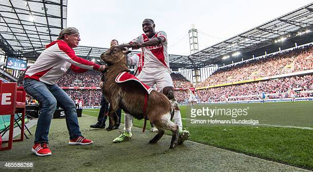 Anthony Ujah of Koeln celebrates his team's fourth goal with mascot Hennes during the Bundesliga match between 1 FC Koeln and Eintracht Frankfurt at...