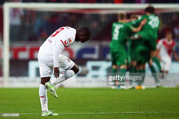 Anthony Ujah of Koeln reacts as Alexander Esswein of Augsburg celebrates his team's second goal with team mates during the Bundesliga match between 1...