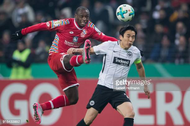 Anthony Ujah of Mainz is challenged by Makoto Hasebe of Frankfurt during the DFB Cup quarter final match between Eintracht Frankfurt and 1 FSV Mainz...