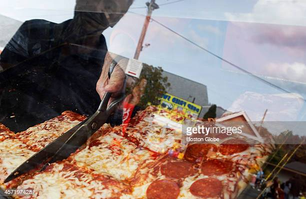 Anthony Valenti uses sheers to cut up a slice of pizza as his relative Anthony Valenti left is reflected in the window of the booth of Boston Garden...