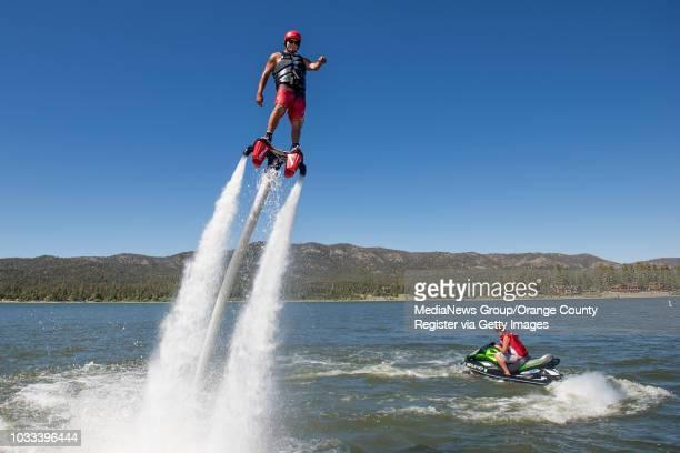Anthony Vargas, left, of Action Aqua Flight demonstrates the fly-board on Big Bear Lake. Donald Hartson, right, powers the water jets from his jet...