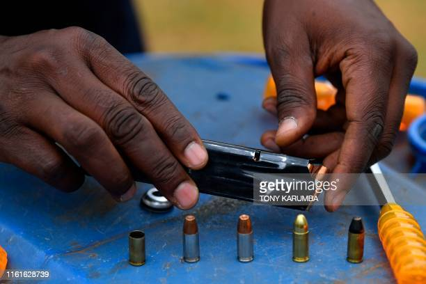 Anthony Wahome Chairman of Kenya's National Gun Owners Association prepares to load a magazine with ammunition including the catridge of a decoupled...