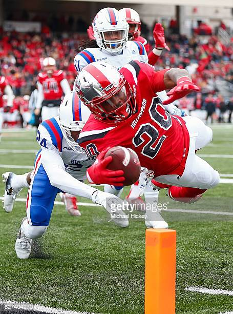 Anthony Wales of the Western Kentucky Hilltoppers dives in the end zone for a touchdown as L'Jarius Sneed of the Louisiana Tech Bulldogs attempts the...