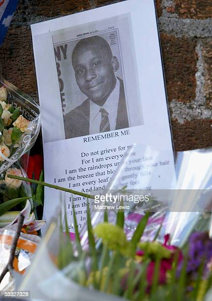 Anthony Walker's photo is seen amongst floral tributes at the scene where the 18yearold died near McGoldrick Park Huyton on August 5 2005 in...