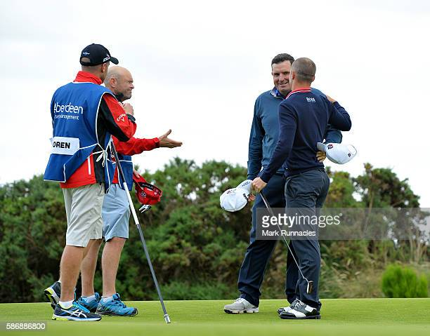 Anthony Wall of England is congratulated by Alex Noren of Sweden and their caddies after he won their match on hole 18 on day four of the Aberdeen...