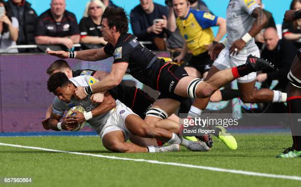 Anthony Watson of Bath dives over for a try despite being held by Owen Farrell and Michael Rhodes during the Aviva Premiership match between Saracens...