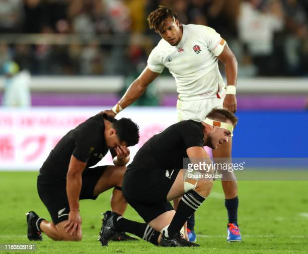 Anthony Watson of England consoles Anton LienertBrown of New Zealand while Sam Cane shows his disappointment after the final whistle during the Rugby...