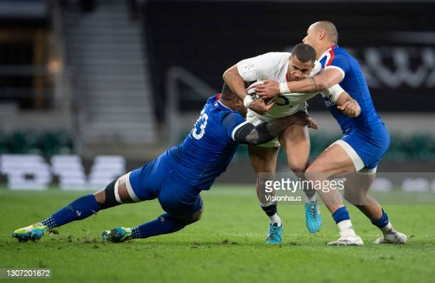 Anthony Watson of England is tackled by Virimi Vakatawa and Gael Fickou of France during the Guinness Six Nations match between England and France at...