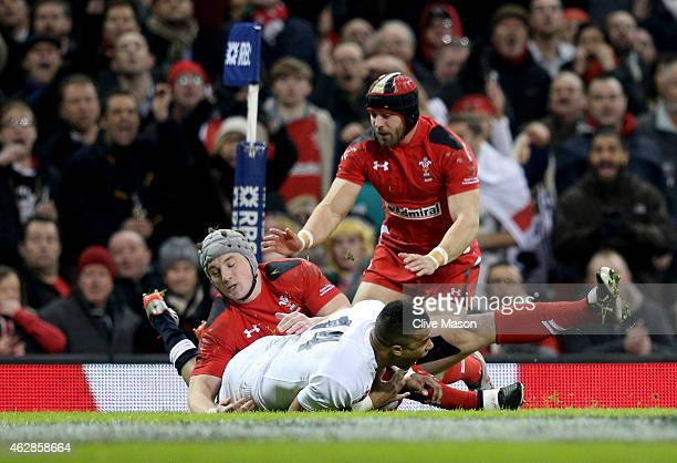 Anthony Watson of England scores his team's opening try despite the tackle from Jonathan Davies of Wales during the RBS Six Nations match between...