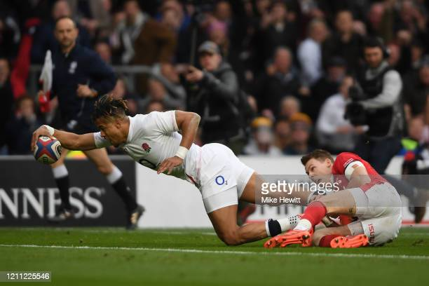 Anthony Watson of England scores the opening try despite the efforts of Liam Williams of Wales during the 2020 Guinness Six Nations match between...