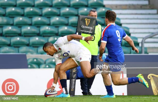 Anthony Watson of England touches down to score their side's first try under pressure from Antoine Dupont of France during the Guinness Six Nations...