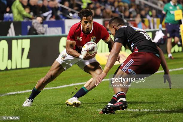 Anthony Watson of the Lions is tackled by Luteru Laulala of the Barbarians on his way to score a try for the Lions during the match between the New...