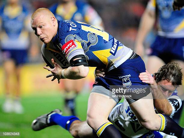 Anthony Watts of the Cowboys is tackled by Brett Kimmorley of the Bulldogs during the round 24 NRL match between the North Queensland Cowboys and the...