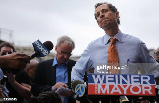 Anthony Weiner listens to a question from the media after courting voters outside a Harlem subway station a day after announcing he will enter the...