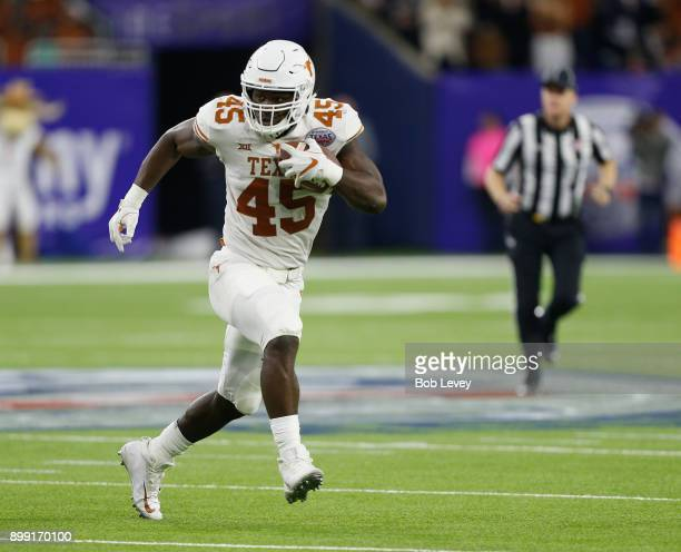 Anthony Wheeler of the Texas Longhorns picks up a fumble and returns for a touchdown against the Missouri Tigers during the Academy Sports Outdoors...