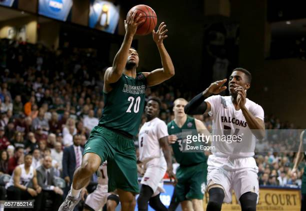 Anthony Woods of Northwest Missouri State University drives past Trevor AndrewsEvans of Fairmont State University during the Division II Men's...