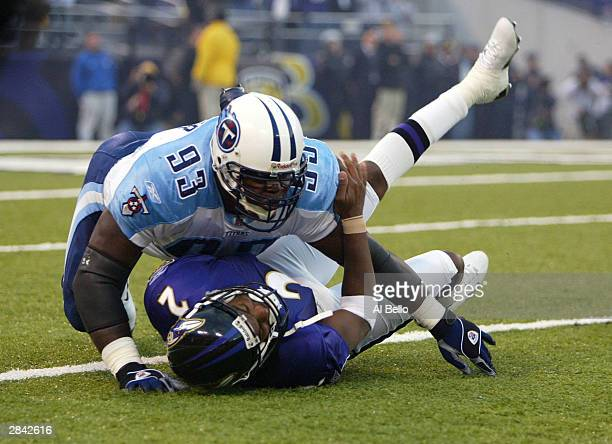 Anthony Wright of the Baltimore Ravens is hit after a throw by Kevin Carter of the Tennessee Titans during their AFC wildcard playoff game at M T...