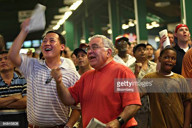 Anthony Yi left and Joe Scalzo center cheer during the 7th horse race at Belmont Park prior to the running of the 140th Belmont Stakes in Elmont New...