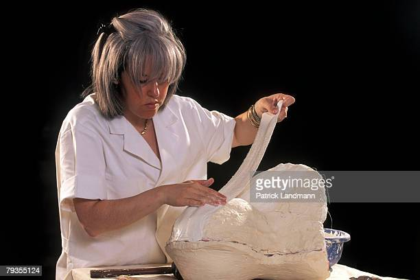Anthropological sculptress Elisabeth Daynes uses the finished clay sculpture of Otzi's skull to make a contact-copy in white silicone with plaster...