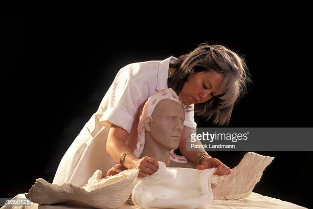 Anthropological sculptress Elisabeth Daynes uses the finished clay sculpture of Otzi's skull to make a contactcopy in white silicone with plaster...