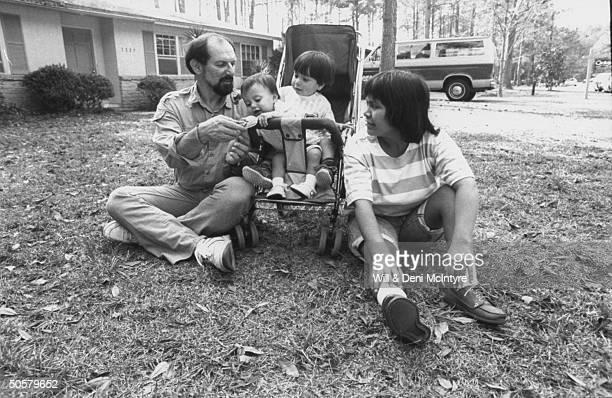 Anthropologist Ken Good w. Yanomamo Indian wife, Yarima & their children David & Vanessa; outside home.