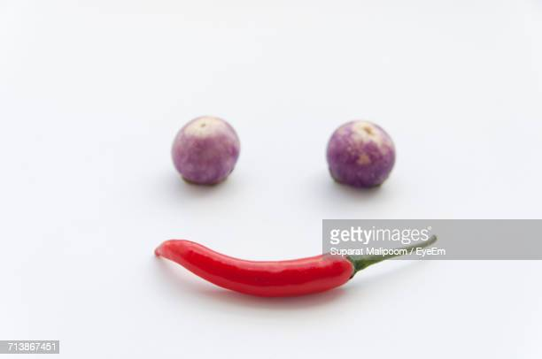 Anthropomorphic Face Made By Red Chili Pepper And Eggplants On White Background