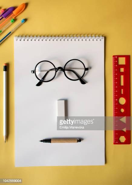 anthropomorphic face made of school supplies on table - occhiali da lettura foto e immagini stock