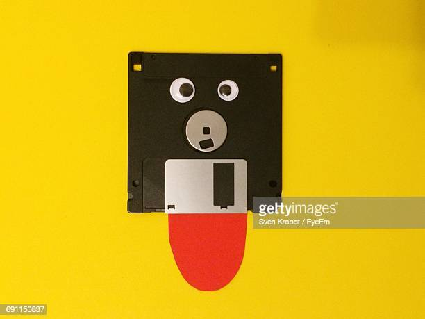 Anthropomorphic Floppy Disk Against Yellow Background
