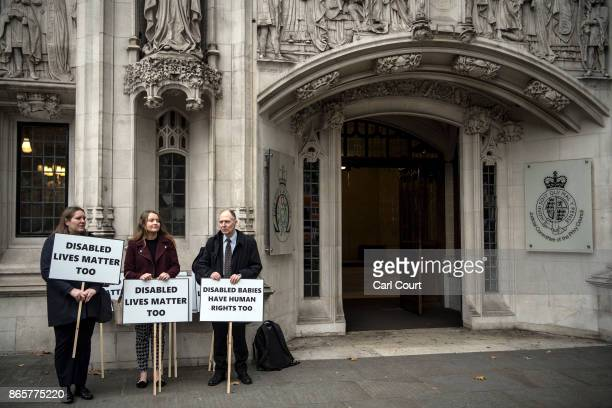 Anti abortion campaigners hold placards as they protest outside the Supreme Court on the first day of a trial in which Northern Ireland's abortion...