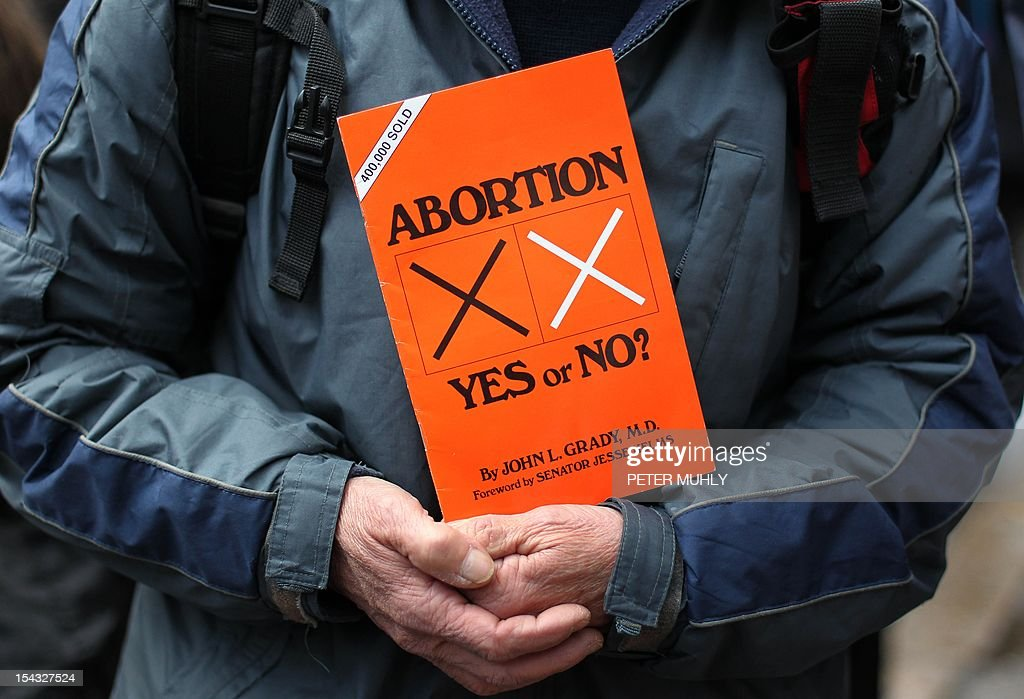 A anti abortion protestors holds up placards outside the Marie Stopes clinic, the first private clinic to offer abortions to women in Belfast, Northern Ireland on October 18, 2012. Dozens of pro-life campaigners protested outside the first abortion clinic in Northern Ireland as it opened to the public. Around 50 protesters brandishing placards saying 'Life is precious' and showing photographs of foetuses gathered outside the privately run clinic in an anonymous building in Belfast. AFP PHOTO/ Peter Muhly