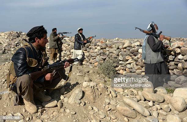 Anti armed Afghan militia forces keep watch during ongoing clashes with Islamic state fighters in Achin district of Nangarhar province on December 27...