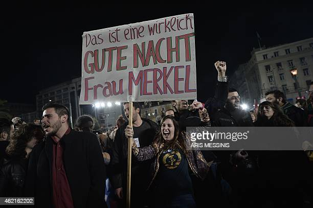 Anti austerity Syriza party supporters one of them holding a placard reading 'This is a real 'Gute Nacht' Frau Merkel' celebrate folllowing the...
