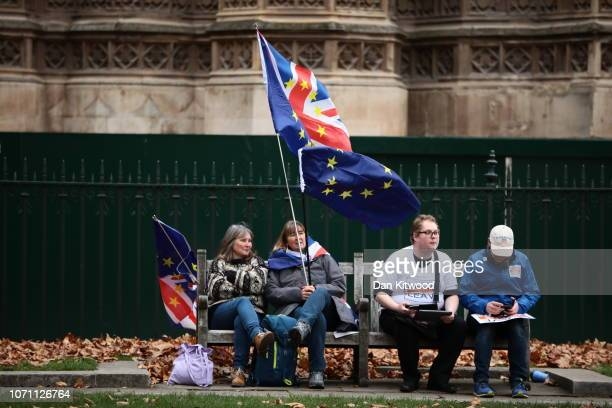 Anti Brexit and Leave Means Leave supporters sit next to each other on a bench outside the Houses of Parliament Westminster on December 10 2018 in...