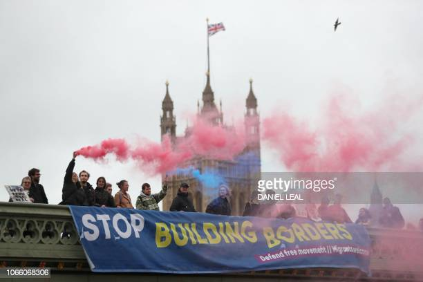 TOPSHOT Anti Brexit demonstrators hold up smoke canisters as they attach a banner to Westminster bridge in central London in support of migration on...