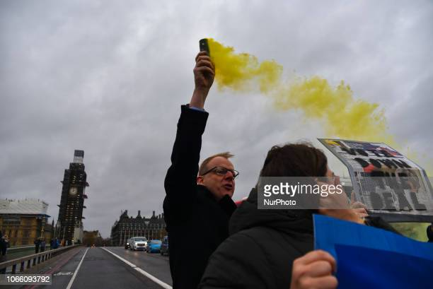 Anti Brexit demonstrators protest holding a banner reading 'Stop Building Borders' and wave flare as they block the traffic on Westminster Bridge on...