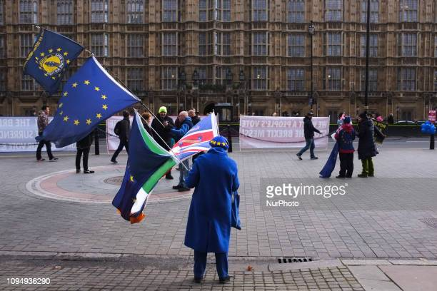 Anti Brexit demonstrators wave EU and Union Flags outside the Houses of Parliament ahead of Prime minister Theresa May's meeting with EU Council...