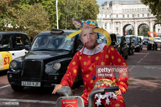 Anti Brexit protester dressed up as a clown version of Prime Minister Boris Johnson hires a 'Boris' bike in Westminster and cycles along The Mall as...