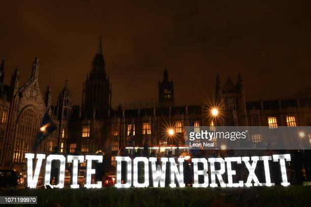 Anti Brexit protesters use illuminated signs as they demonstrate with placards outside the Houses of Parliament Westminster on December 10 2018 in...