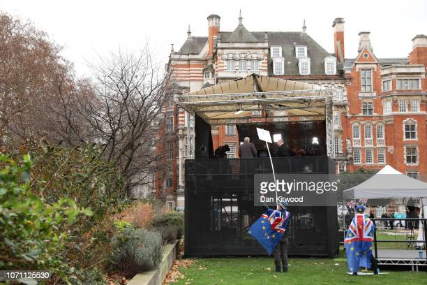 Anti Brexit supporters hold up placards by a makeshift TV Studio outside the Houses of Parliament in Abingdon Street Gardens Westminster on December...