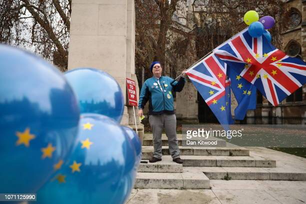 Anti Brexit supporters with flags and balloons protest outside the Houses of Parliament Westminster on December 10 2018 in London England The Prime...
