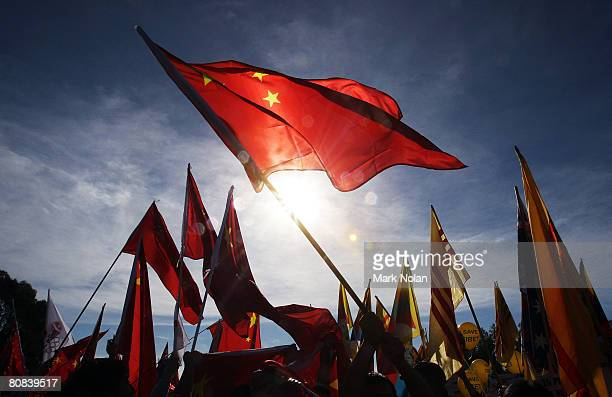 Anti Chinese protesters and pro Chinese people wave flags as they are separated by police during the Olympic Torch relay at Parliament House on April...