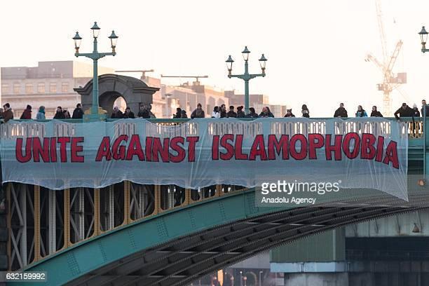 Anti Donald Trump demonstrators drop a banner reading Unite Against Islamophobia over Southwark Bridge in London England UK on January 20 2017 The...