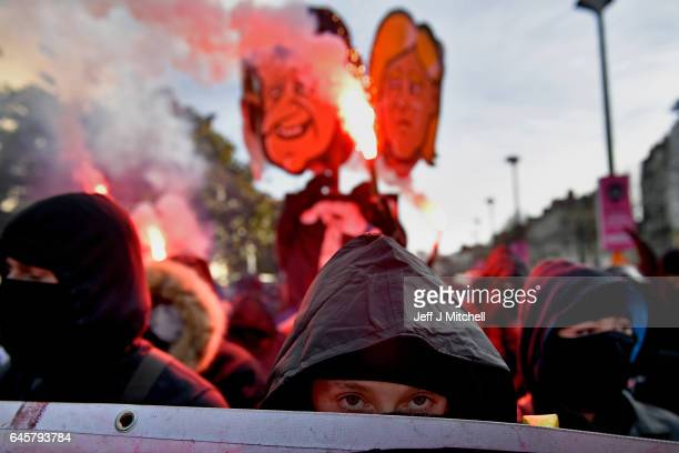Anti establishment demonstrators hold flares during protests ahead of a presidential campaign rally by National Front Leader Marine Le Pen on...